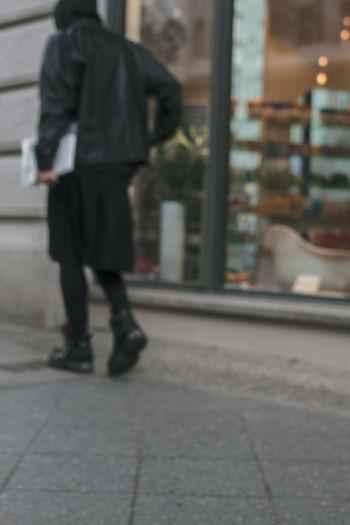 Rear view of woman walking on sidewalk in city