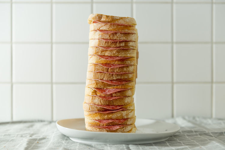 Close-Up Of Bread Stack With Salami In Plate On Table