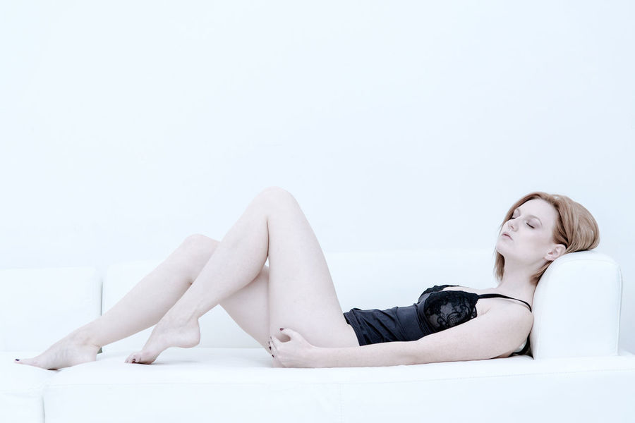 Beautiful Woman Adult Adults Only Attractive Beautiful Woman Beauty Caucasian Charming Clean Copy Space Day Emotional Full Length Glamour Indoors  Leisure Activity Lingerie Lying Down One Person One Woman Only One Young Woman Only People Portrait Relaxation Relaxed Seductive Sitting Studio Shot White Background Women Young Adult Young Women