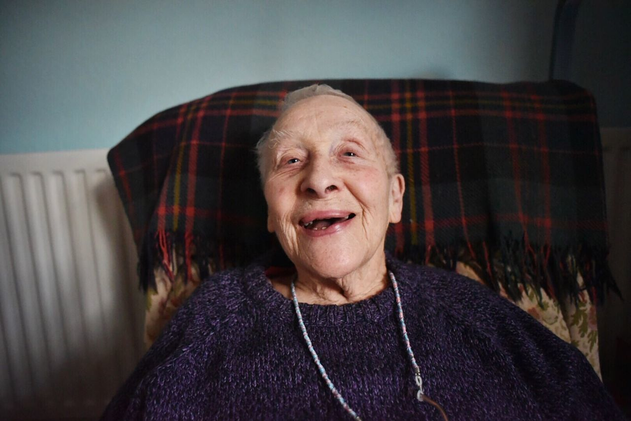 Portrait of happy senior woman resting on sofa at home
