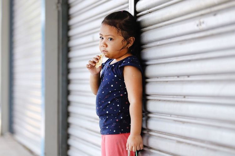 Girl eating food while standing by shutter