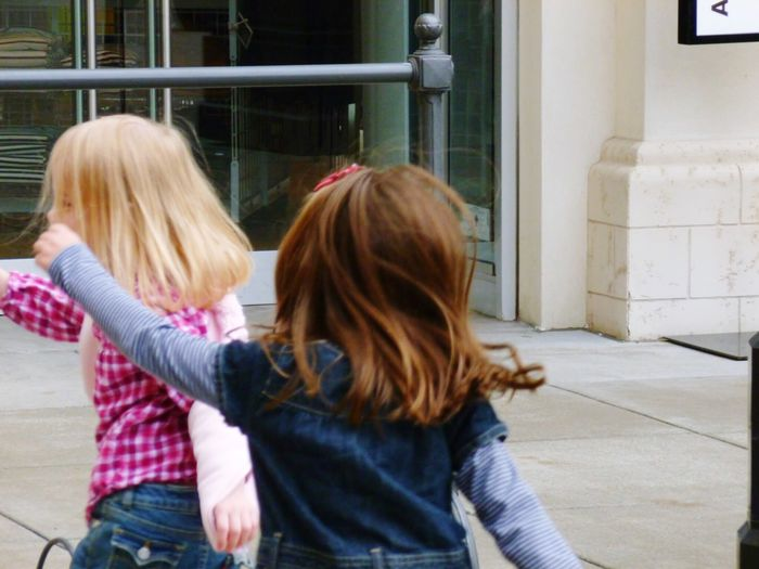 Premium Collection Two People Real People Rear View Togetherness Day Bonding Selected For Premium. Selected For Premium Girls Blond Hair Brown Hair Running Fun October Day Outdoors Outside Denim Jeans Denimjeans Elementary Age Arms Swinging Long Hair Arms Outstretched Arms In Motion