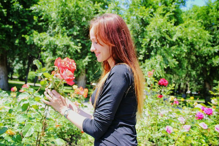 Side view of young woman with flowers in park