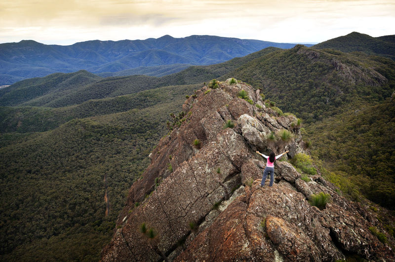 High angle view of woman with arms raised standing on mountain against sky