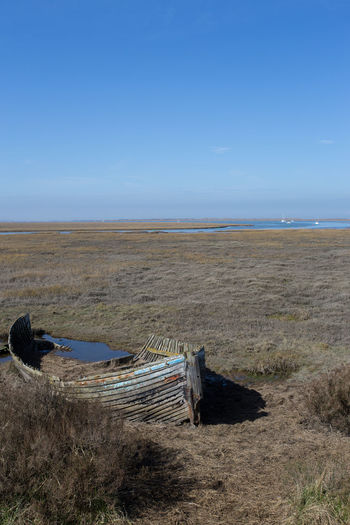 An old abandoned boat on the salt marshes near Blakeney, Norfolk, England, UK Copy Space Salt Marsh Beauty In Nature Blakeney Blue Boat Day Environment Horizon Horizon Over Water Land Landscape Nature No Clouds In The Sky No People Non-urban Scene Outdoors Rotting Scenics - Nature Sea Sky Tranquil Scene Tranquility Water
