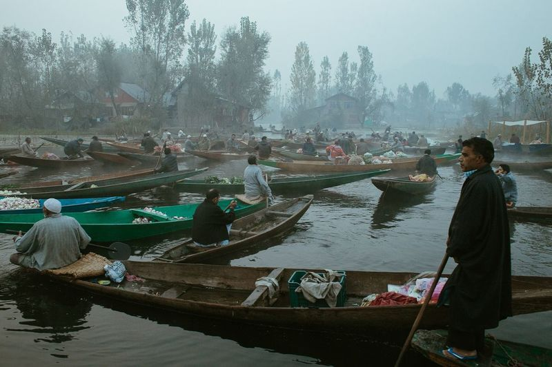 People working on boat in lake against sky