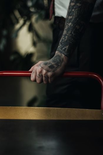 Cropped tattooed hand of man holding railing