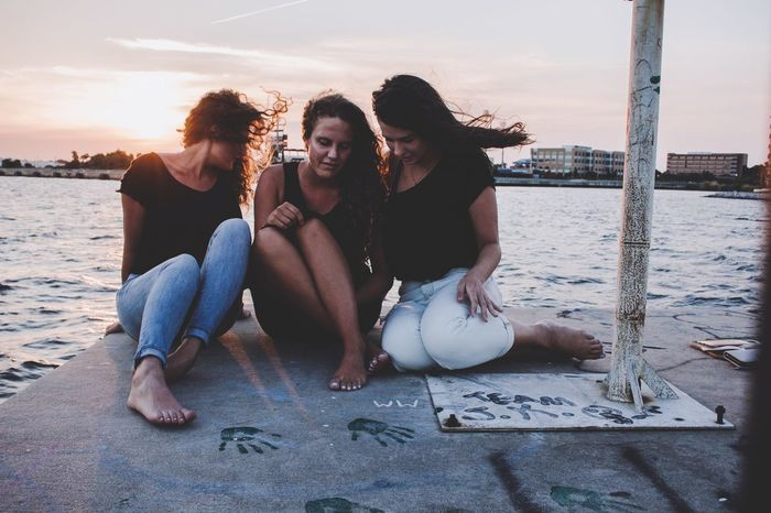 Stay close to people who feel like sunlight Portrait Candid Photography Candid Brunette Blonde Sky Tangled Tan Sisters Black Curly Hair Summer Dock Dockside Water Leisure Activity Lifestyles Real People Togetherness Sea Sky Young Adult Young Women Friendship Sitting People Positive Emotion Beach Emotion Women