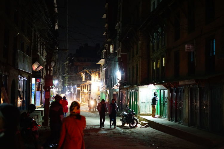 People on street amidst buildings at night