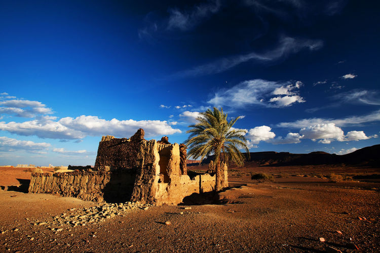 Built Structure By Atlas Mountains At Erg Chebbi Against Sky