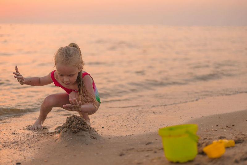 Full length of girl on beach during sunset