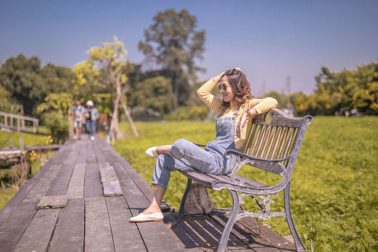 Woman sitting on seat against sky