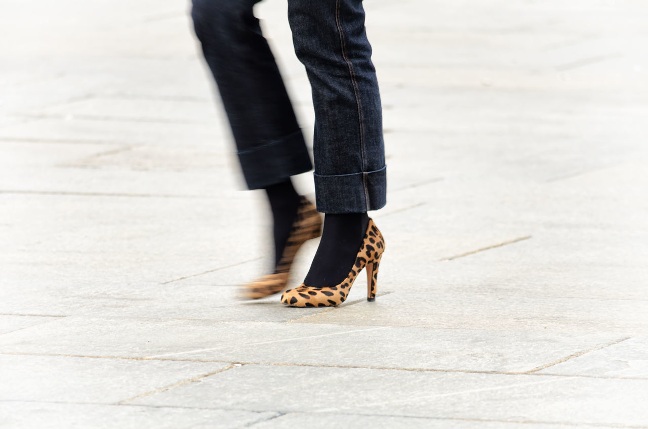Low section of woman wearing high heels on street