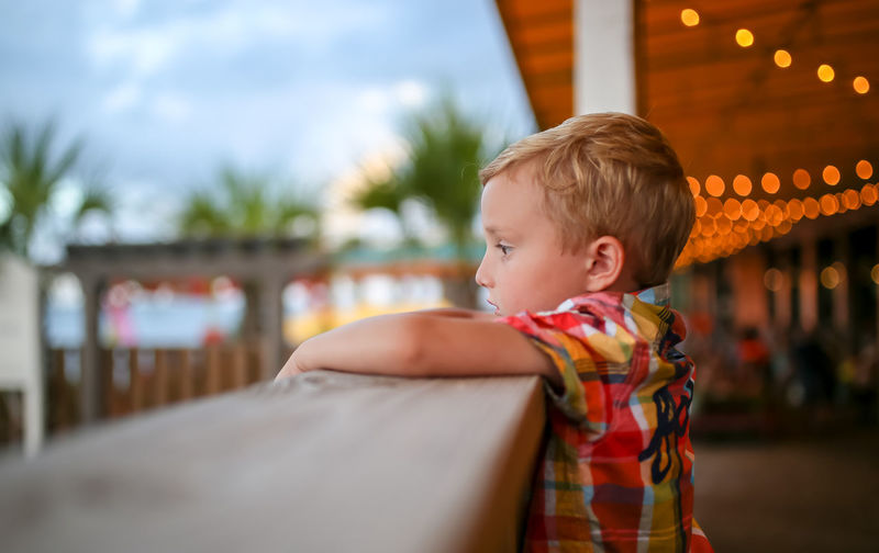 Boy looking over balcony with bokeh in the background Child Childhood One Person Real People Leisure Activity Side View Focus On Foreground Innocence Looking Away Outdoors Cute Bokeh Bokeh Photography Bokehlicious Bokeh Lights Boy Balcony Beach Summer Summertime Patio Outdoor Eating