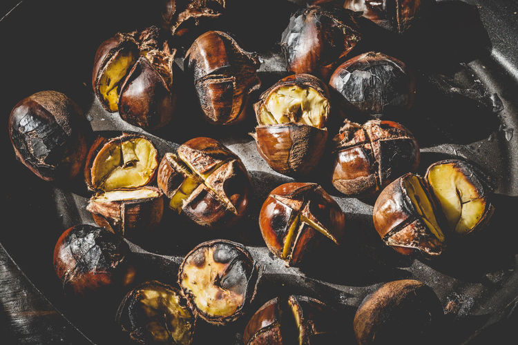 Close up of Roasted chestnuts in iron grilling pan over rustic wooden table, top view. Autumn Chestnut Chestnuts Cooking Iron Meal Snack Brown Food Fried Fruit Gourmet Healthy Heap Ingredient Nut Opened Pan Roasted Roasting Seasonal Sweet Tasty Traditional Wooden