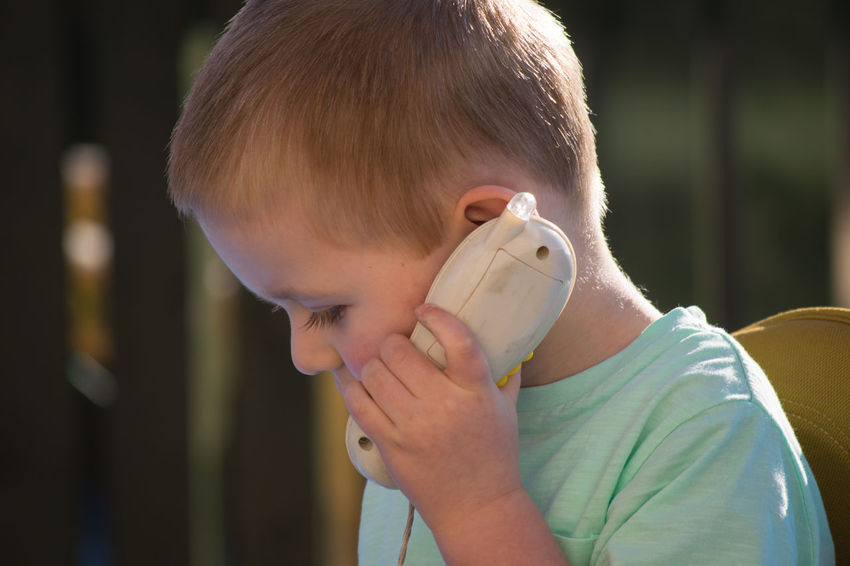 Blonde Boy Child Caucasian Playing Toy Phone Plastic Human Hand Human Hair Human Face Portrait Outdoors Outside Day Horizontal Childhood Close-up Colour Image Headshot Real People Memories One Child One Person Human Meets Technology