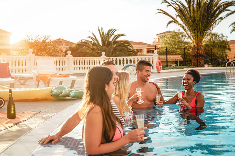 Friends making pool party Happy People Youth Lifestyles Millennials Drinking Champagne Summer Pool Party Swimming Pool Group Of People Young Adult Water Holiday Trip Smiling Vacations Women Men Adult Happiness Food And Drink Tree Glass