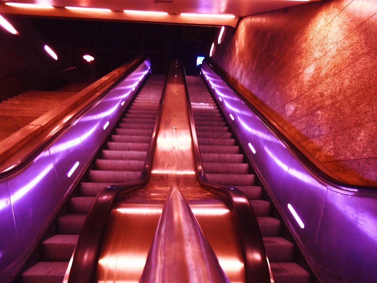VIEW OF ESCALATOR IN ILLUMINATED UNDERGROUND