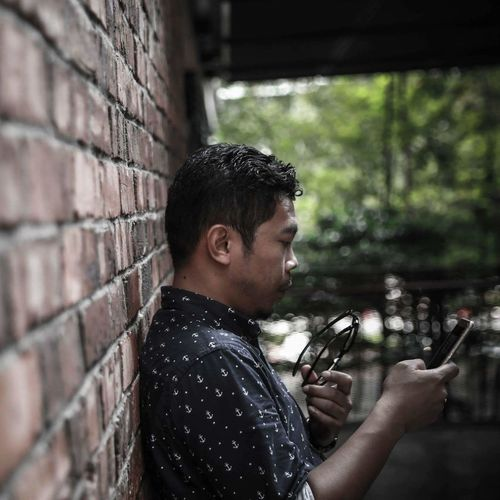 Side view of man using phone by wall