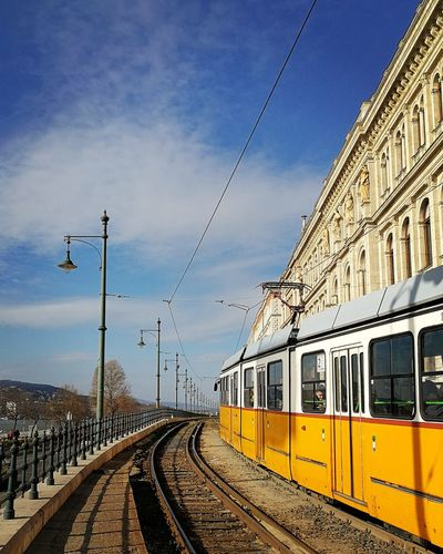 Yellow Train On Bridge By Building Against Sky