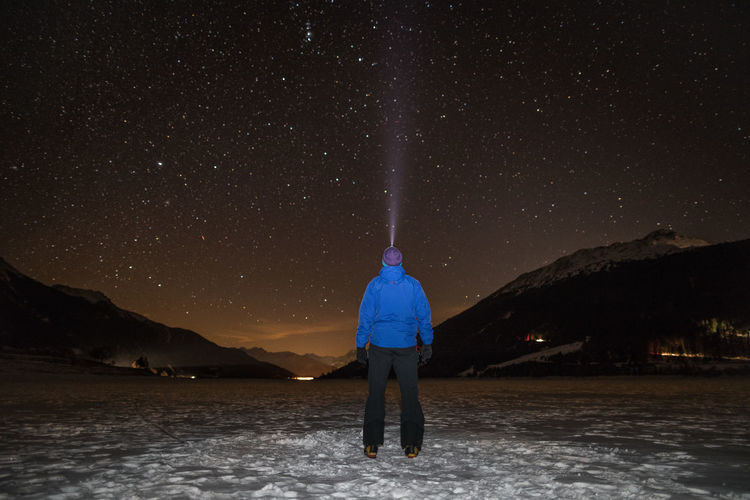 Rear view of hiker standing on frozen lake against starry field at night during winter
