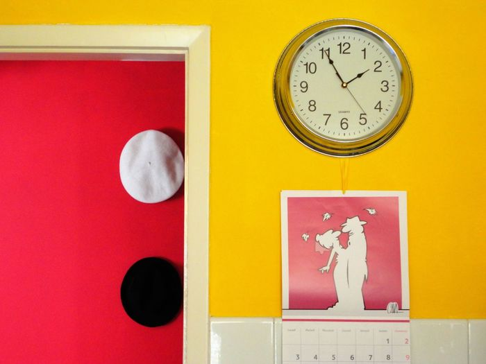 Wall clock over poster at home