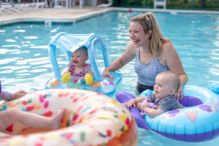 Mother with children on inflatable rings in swimming pool