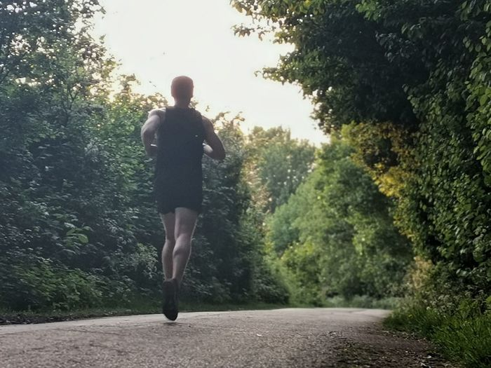 Rear view of man running on road amidst trees
