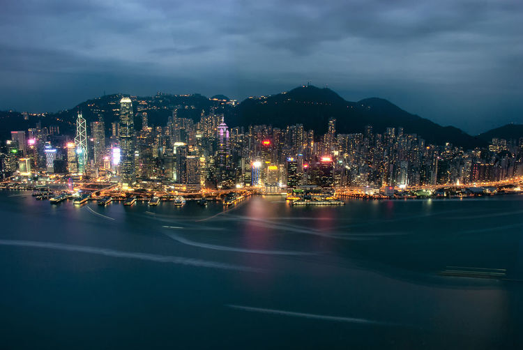 The illuminated skyscrapers along the waterfront at victoria harbour in hong kong