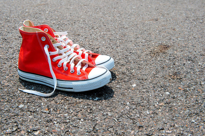 Red sneakers on black background. Absence Beach Canvas Shoe Close-up Day High Angle View Ice Skate Nature No People Outdoors Pair Red Sand Shoe Shoelace Soccer Shoe Sport Things That Go Together