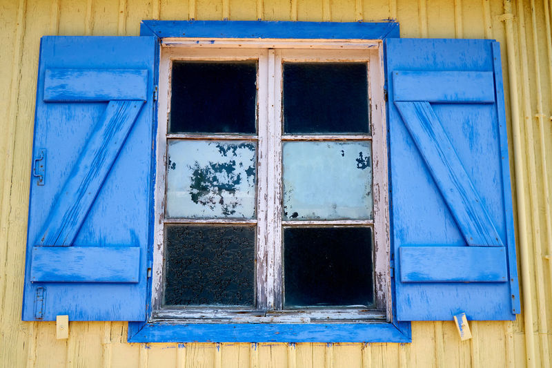 Low angle view of blue window on old building