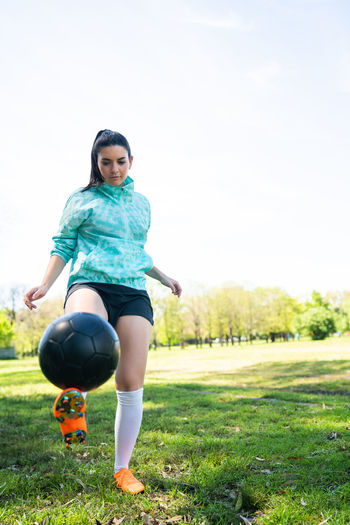Full length of young woman playing soccer on field against sky