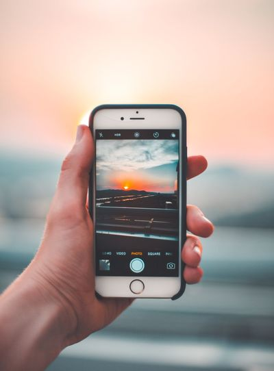 Human Hand Holding Real People Wireless Technology Smart Phone Focus On Foreground Technology Portable Information Device Mobile Phone Lifestyles Sunset Human Body Part Communication Sky Screen Digital Display Photographing One Person Device Screen Photography Themes