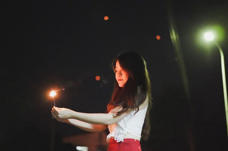 Beautiful woman holding sparkler at night