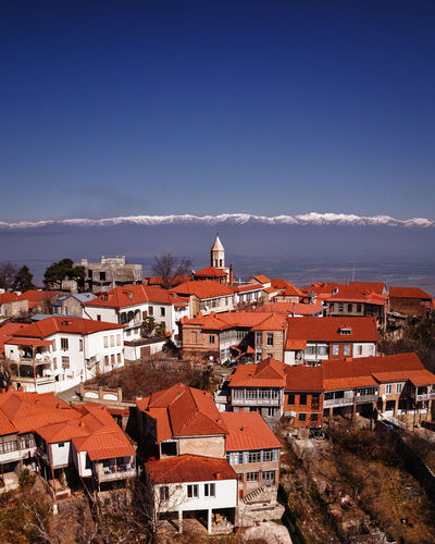 High angle view of townscape against blue sky and mountains