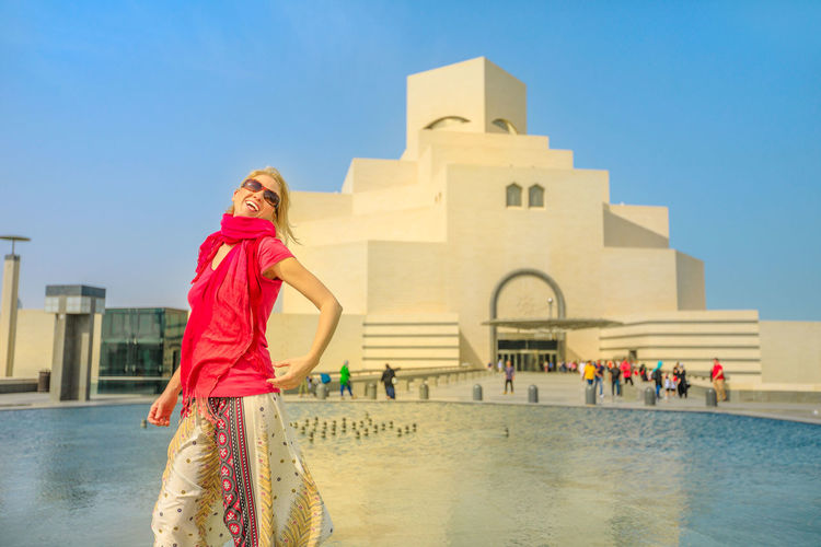 Carefree woman sitting in front of fountain of famous museum along the Corniche near Dhow Harbor in Qatari capital. Caucasian tourist enjoying in Doha, Middle East, Arabian Peninsula in Arabian Gulf. Doha Doha,Qatar Qatar City Town Waterfront Sea Skyline Woman Model Girl Female Tourist Seascape Tourist Attraction  The Pearl, Doha The Pearl Cityscape Holiday Vacation People Museum Fountain Built Structure Architecture One Person Building Exterior Water Women Real People Sky Looking At Camera Standing Lifestyles Building Leisure Activity Clear Sky Day Portrait Nature Hair Hairstyle