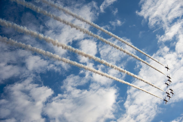 Low angle view of airplane emitting vapor trail against blue sky