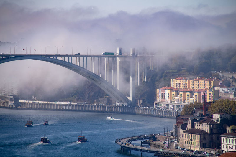 Sea fog over the Arrabida Bridge Porto Oporto Porto Portugal 🇵🇹 Architecture Arrangement Bridge Bridge - Man Made Structure Building Exterior Built Structure City Cityscape Connection Fog Nature Nautical Vessel No People Outdoors River Sea Fog Sea Mist Sky Transportation Travel Destinations Tree Water Waterfront