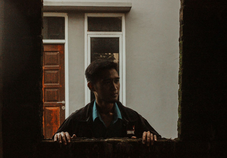 Portrait of man looking through window at home