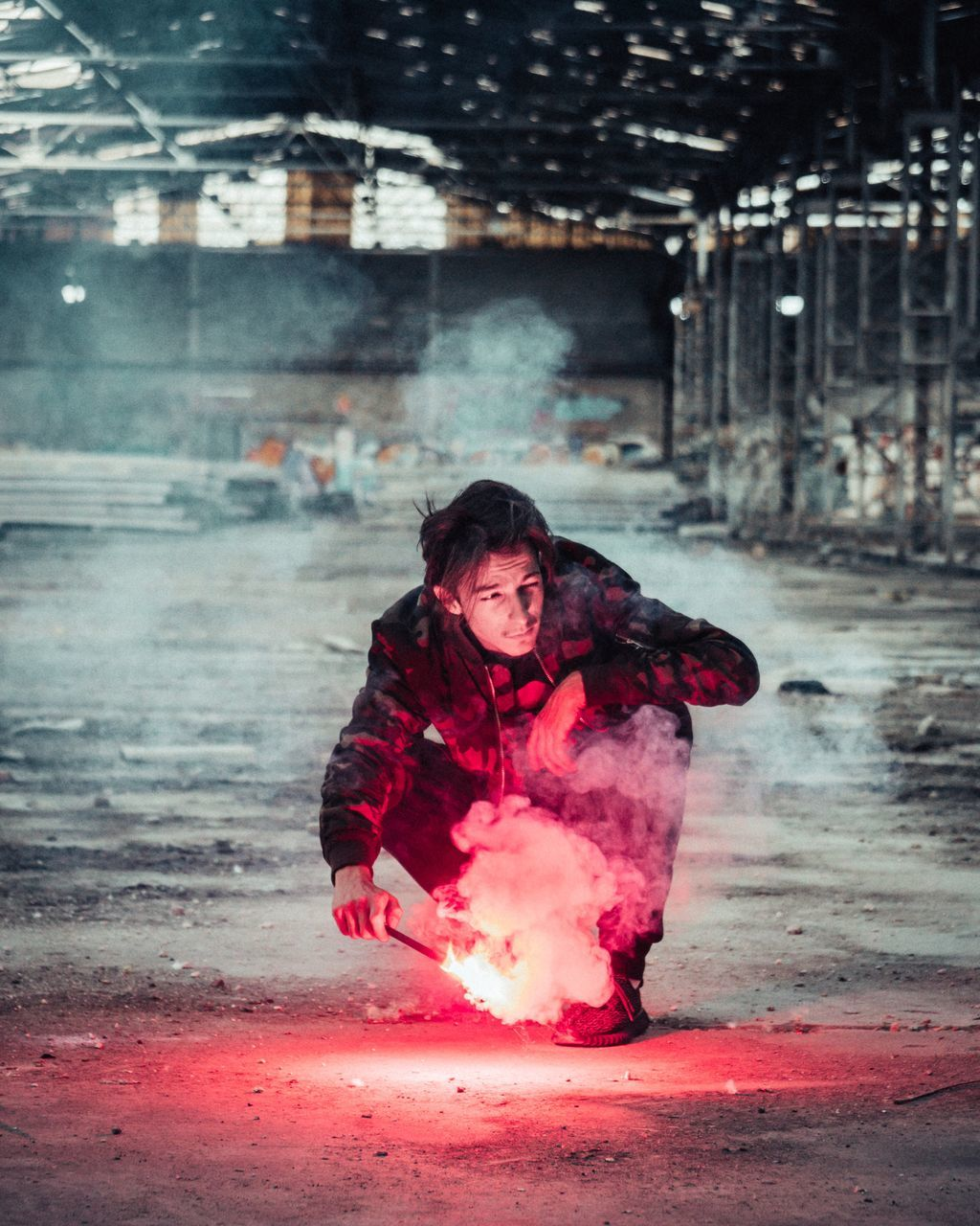 Man Holding Sparkler While Crouching In Factory