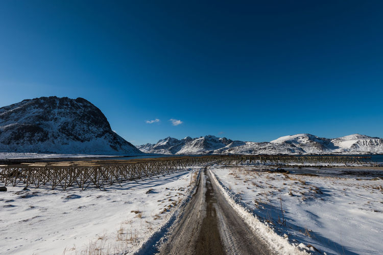 Road leading towards snowcapped mountains against blue sky