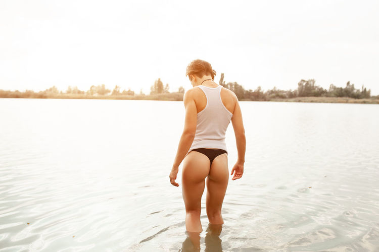 Rear view of sensuous woman standing in sea against sky
