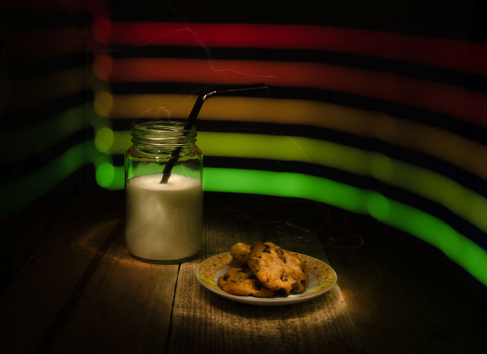 Milk in glass jar with cookies on table