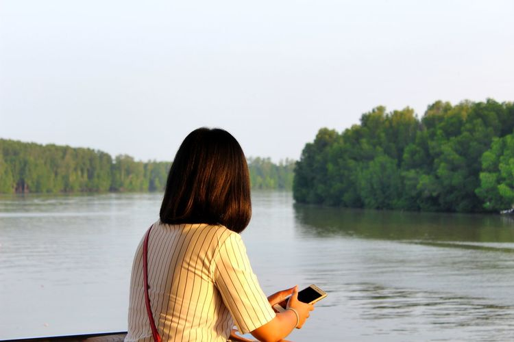 Rear view of woman using phone while standing by lake against clear sky