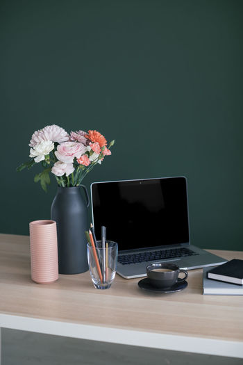 Flower vase by laptop on table at home