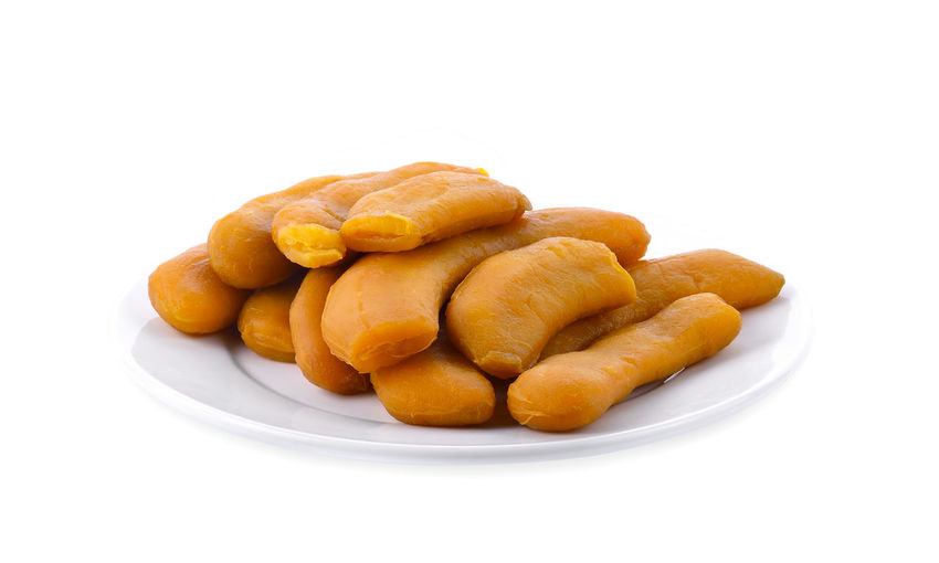 Close-up of tamarind in plate on white background