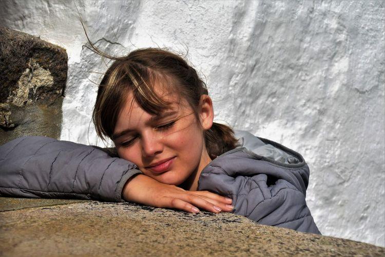 Portrait of woman lying on rock against wall