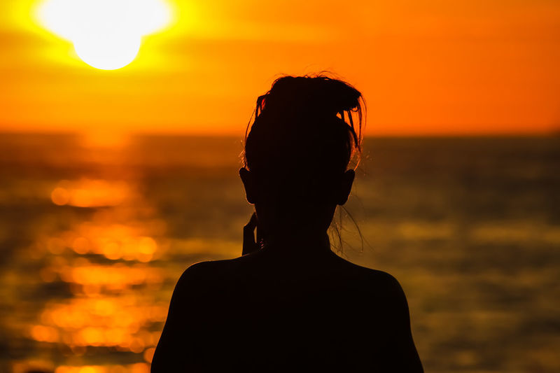 Rear view of silhouette woman against sea during sunset