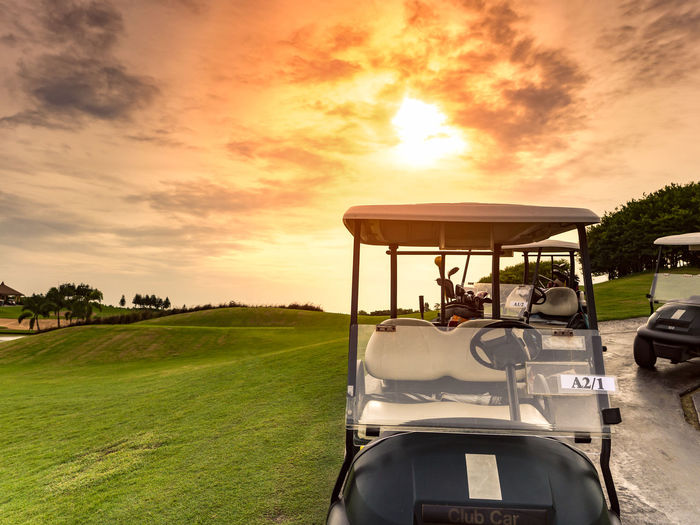 Golf carts or golf club cars in a beautiful golf course with sunset or sunrise background in summer Beauty In Nature Day Field Golf Golf Cart Golf Course Grass Green - Golf Course Landscape Nature No People Outdoors Scenics Sky Sport Sunset Transportation Tree