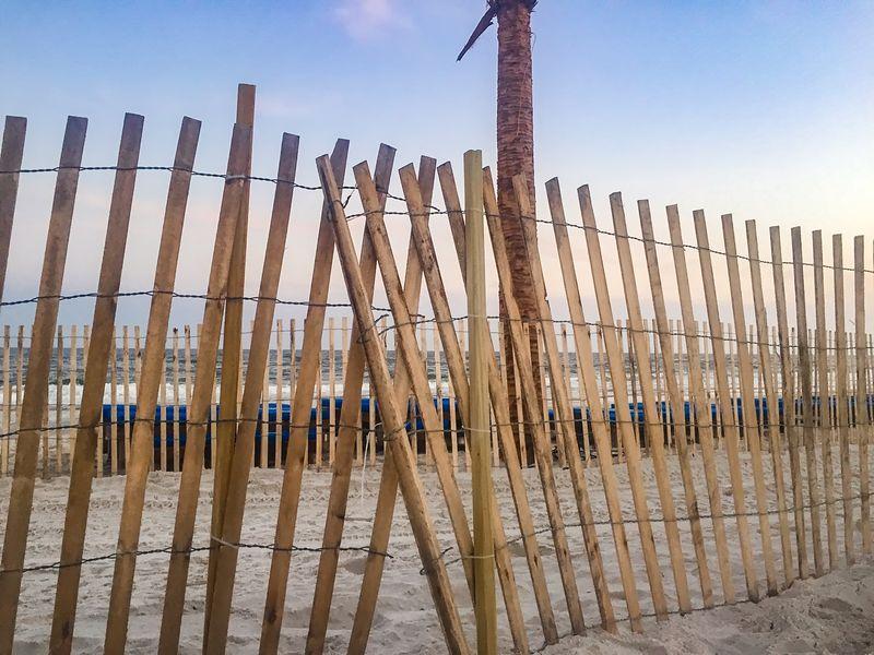 fence on the beach Beach Life Orange Beach Wooden Fence Beach Beach Fence Day Fence No People Ocean Outdoors Sand Sand & Sea Sand Dune Sky Sunset Waves Wooden Post